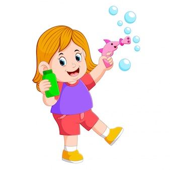A menina está brincando com a bolha e segurando a garrafa verde