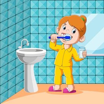 A menina está escovando os dentes no banheiro antes de dormir
