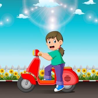A menina está montando a scooter vermelha na estrada no dia