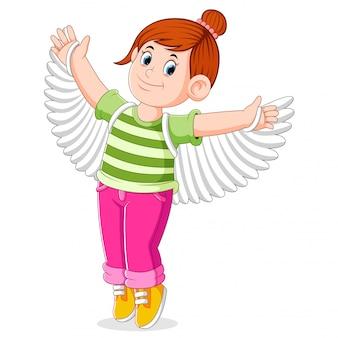 A menina está tentando as asas falsas para preparar a dança