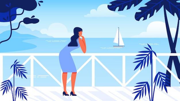 A mulher está no beira-rio parece o mar e o veleiro.