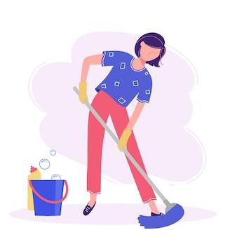A mulher faz a limpeza esfregando o chão com uma vassoura.
