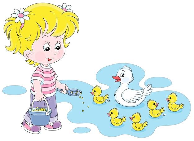 A pequena agricultora de pé com um balde de grãos para ração e alimentando uma ninhada alegre de pequenos patinhos amarelos e um pato branco fofo em um lago