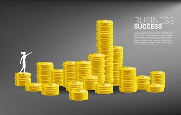 A silhueta da mulher de negócios aponta para a frente à pilha de moeda. conceito do negócio do crescimento, sucesso no trajeto de carreira.