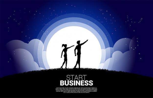 A silhueta da mulher de negócios e do homem de negócio aponta para a frente adiante na noite. conceito de missão de visão e empreendedor