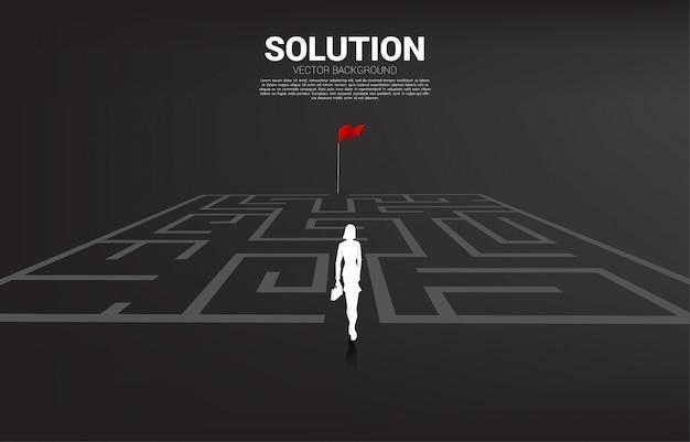 A silhueta da mulher de negócios entra ao labirinto à bandeira vermelha. conceito de negócio para encontrar a solução e alcançar a meta