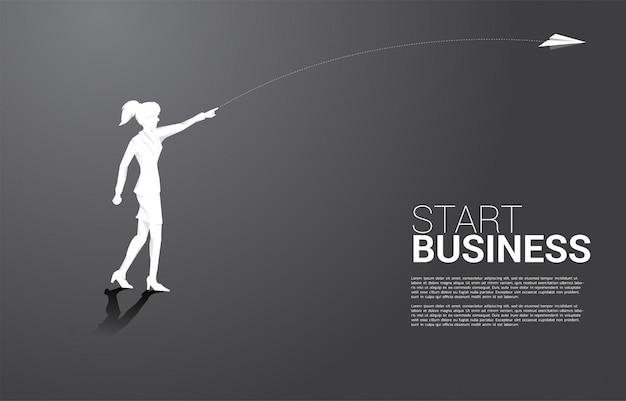 A silhueta da mulher de negócios joga para fora o avião de papel do origâmi. conceito de negócio de iniciar negócios e empresário