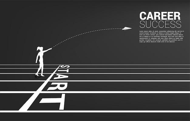 A silhueta da mulher de negócios joga para fora o avião de papel do origâmi da linha de começo na pista de atletismo. conceito de negócio de iniciar negócios e empresário