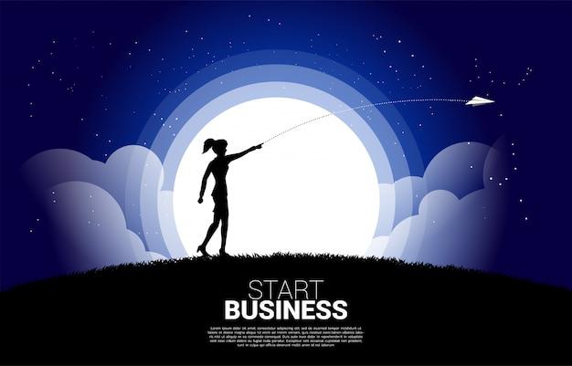 A silhueta da mulher de negócios joga para fora o avião de papel do origâmi na noite.