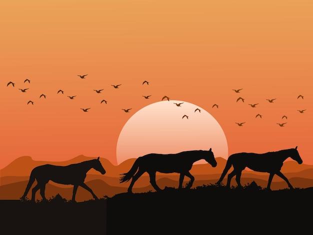 A silhueta de uma manada de cavalos nas colinas ao pôr do sol tem montanhas e céu laranja como pano de fundo