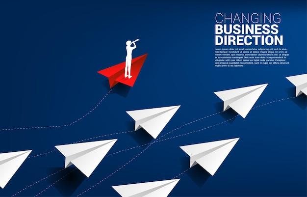 A silhueta do empresário olhando através do telescópio em pé no avião de papel origami vermelho é mover a direção do grupo de brancos. conceito de negócio de disrupção e marketing de nicho