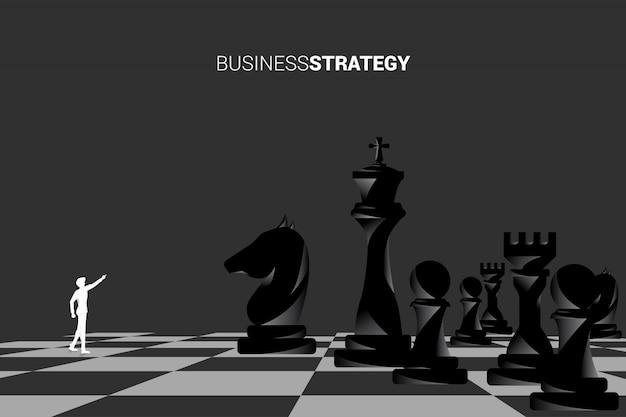 A silhueta do homem de negócios aponta para a frente com parte de xadrez.