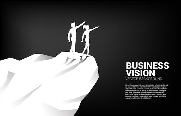 A silhueta do homem de negócios e da mulher de negócios aponta para a frente do penhasco da montanha. conceito de missão de visão de mercado de negócios start up