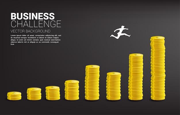 A silhueta do homem de negócios salta à coluna mais alta do gráfico do dinheiro. conceito de risco, sucesso e crescimento nos negócios