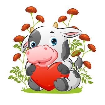 A vaca fofa com o chifre pequeno está sentada no jardim segurando a boneca do amor colorida da ilustração