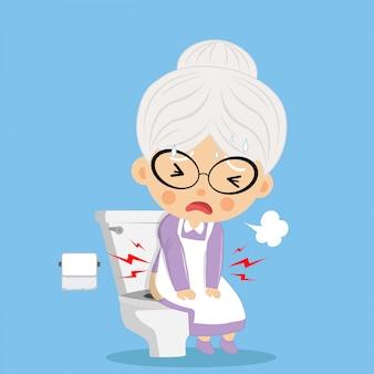 A velha estava defecando no banheiro com dificuldade e séria como má saúde.