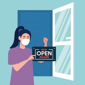 Aberto novamente após quarentena, mulher com etiqueta de reabertura de loja e porta aberta, estamos abertos novamente