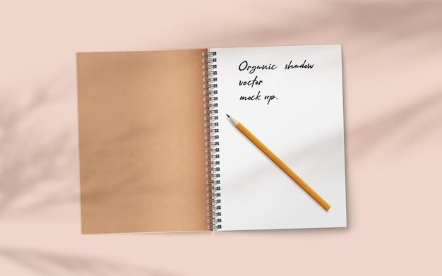 Abra o caderno realista com lápis sobre fundo bege delicado suave abstrato caindo sobreposição de sombra da planta. espaço em branco do diário aberto para o seu texto. papel de caderno de modelo de vetor realista.