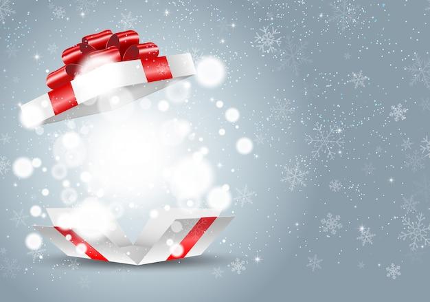 Abriu a caixa de presente branca com laço vermelho e luzes no fundo do floco de neve