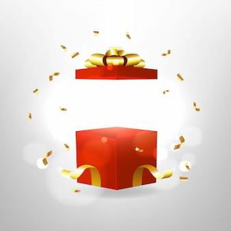 Abriu a caixa de presente vermelha com laço vermelho e fita de ouro.