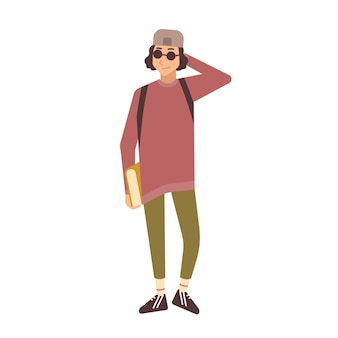 Adolescente estiloso sorridente usando boné e óculos escuros e segurando livros didáticos