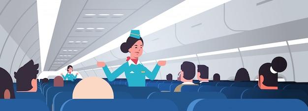 Aeromoça, explicando as instruções para os passageiros comissárias de bordo em uniforme, mostrando saídas de emergência conceito de demonstração de segurança interior do avião placa horizontal