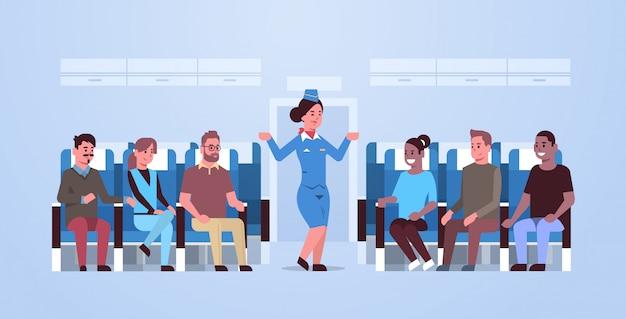 Aeromoça, explicando as instruções para passageiros de corrida de mistura aeromoça em mãos gesticulando uniformes mostrando saídas de emergência conceito de demonstração de segurança placa de avião interior horizontal