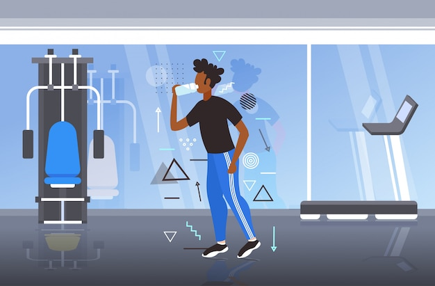 Afro-americano aptidão atleta homem beber água de garrafa de plástico após treino exercitar estilo de vida saudável conceito moderno ginásio interior horizontal comprimento total