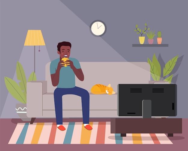 Afro-americano come um hambúrguer, segura uma cerveja e assiste tv no sofá.