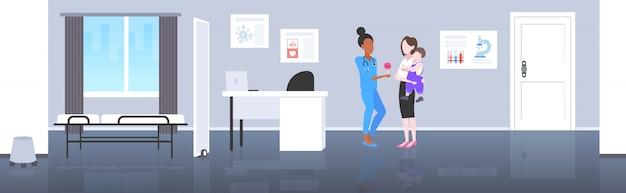 Afro-americano médico pediatra dando pirulito consulta menino conceito de saúde mãe segurando o bebê nas mãos escritório moderno hospital interior comprimento total horizontal