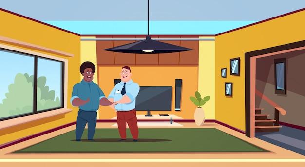 Agente de dois homens e novo proprietário na moderna sala de estar, apertando as mãos, comprando o conceito de casa