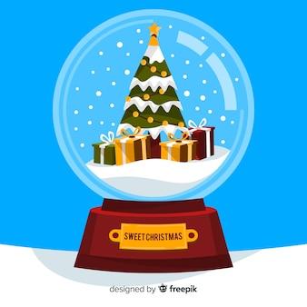 Agitando o globo com árvore de natal e presentes