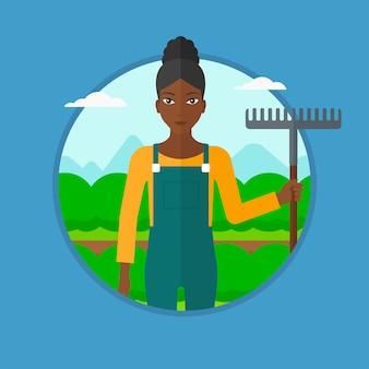 Agricultor com ancinho no campo de repolho.