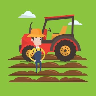 Agricultor em pé com o trator no fundo.