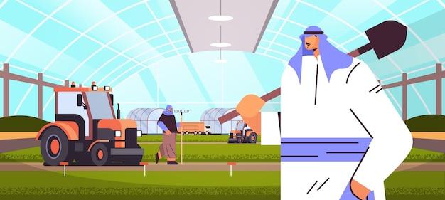 Agricultores árabes e tratores trabalhando em produtos orgânicos plantação industrial plantas de cultivo agricultura inteligente conceito de agronegócio com efeito de estufa interior ilustração vetorial horizontal