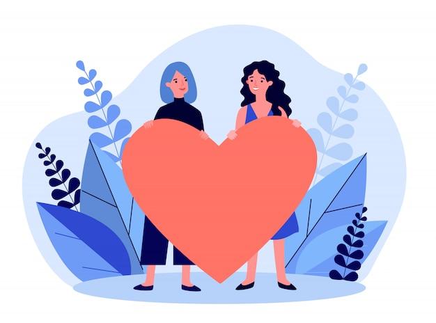 Alegre casal gay feminino segurando coração vermelho