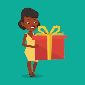 Alegre mulher africana segurando a caixa com presente.