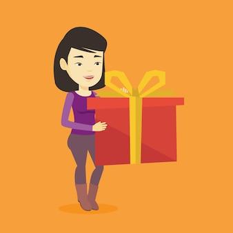 Alegre mulher asiática segurando a caixa com presente.