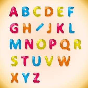 Alfabeto de doces de cores diferentes em fundo de açúcar