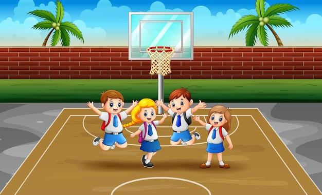 Alunos alegres pulando na quadra de basquete
