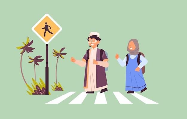 Alunos árabes cruzando a rua na faixa de pedestres com a placa do conceito de segurança rodoviária horizontal