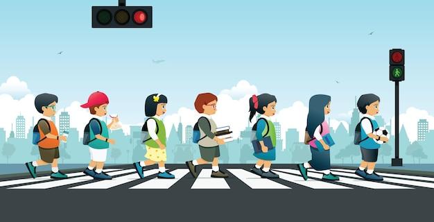Alunos caminhando na faixa de pedestres com semáforos.
