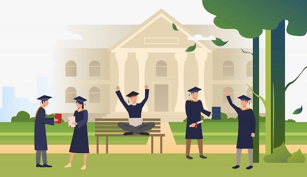 Alunos com diplomas comemorando a formatura no campus park