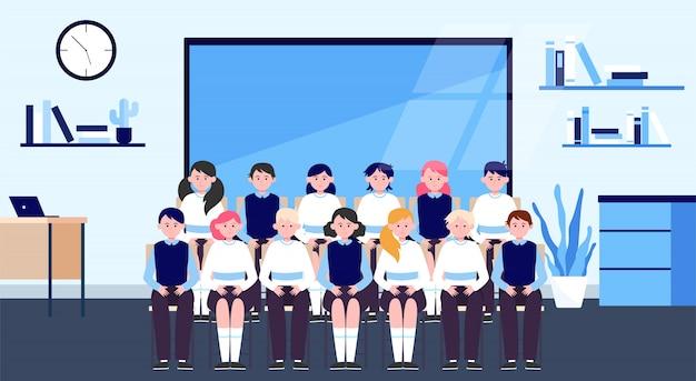 Alunos da escola posando para foto de classe em sala de aula