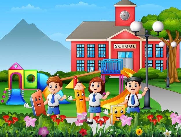 Alunos felizes segurando papelaria no pátio da escola