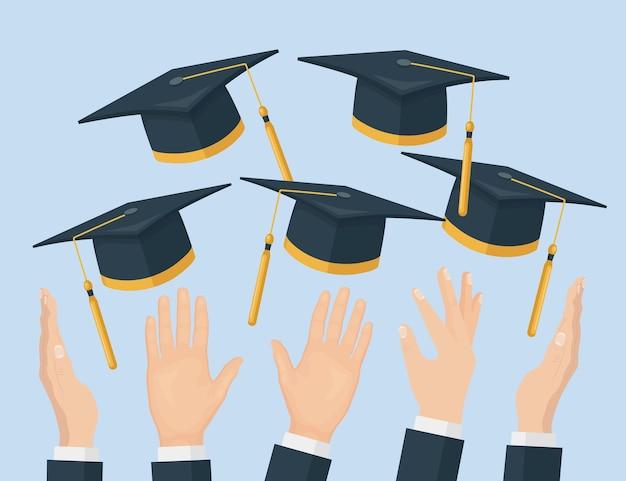 Alunos se formando jogando bonés de formatura para o alto, usando chapéus acadêmicos