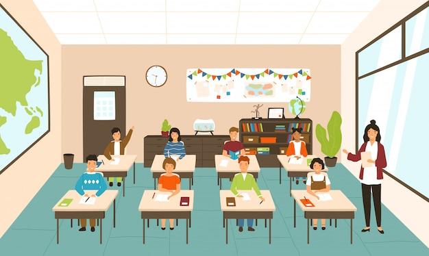 Alunos sentados em mesas na sala de aula moderna, jovem professora ensinando-os.