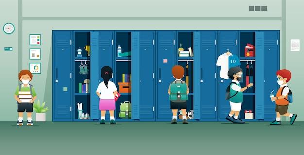 Alunos usando máscaras mantêm seus dispositivos no armário da escola.