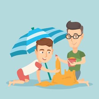Amigos masculinos que constroem o sandcastle na praia.