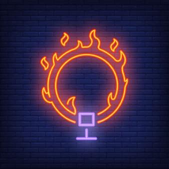 Anel no ícone de néon de fogo. Aro flamejante do circo no fundo escuro da parede de tijolo.